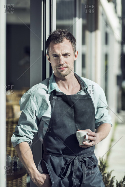 Portrait of confident owner with coffee cup standing at entrance of cafe
