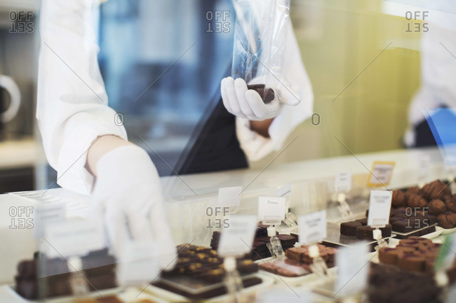 Midsection of female worker packing sweet food at display cabinet in cafe