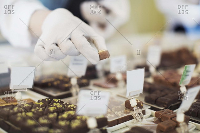 Cropped image of worker holding sweet food at display cabinet at cafe
