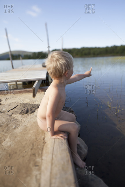 Naked boy sitting at lake