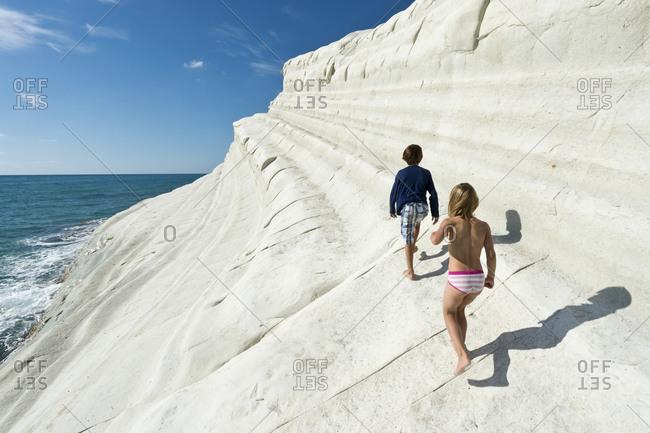 Children walking on white cliff