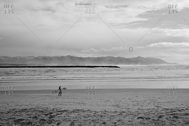 Surfer walking on a sandy beach