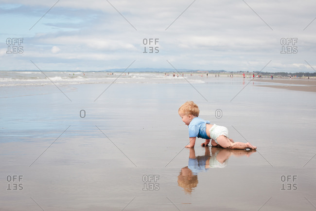 Young boy crawling an the sand at beach