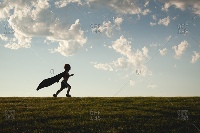 Silhouette of a young boy running wearing a cape