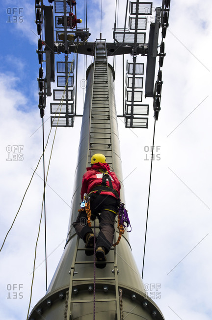 Man on ladder climbing up pole
