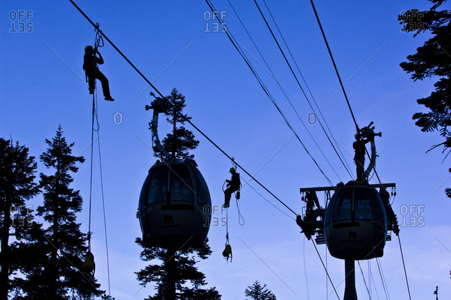 Silhouettes on men repairing a cable car line