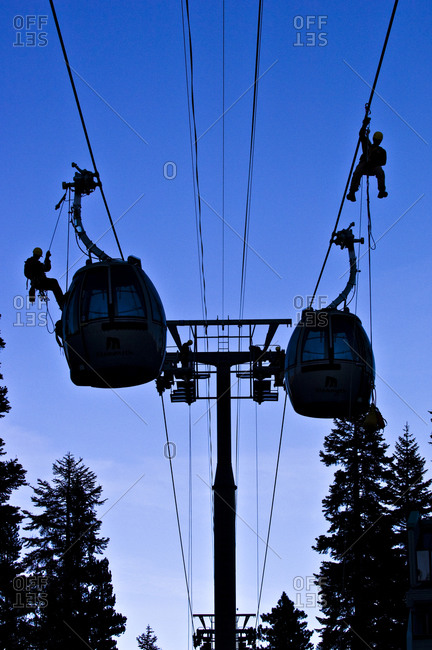 Silhouettes on men fixing a cable car line