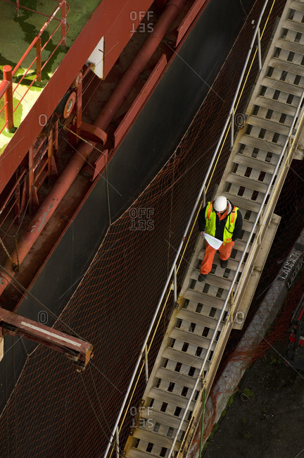 Worker walking down stairs next to ship