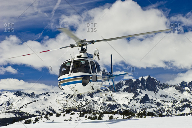 Helicopter taking off in snowy mountains