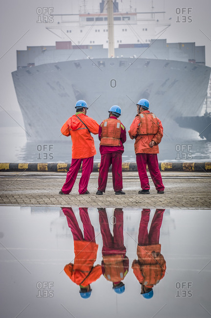 Three workers waiting for a ship to come in