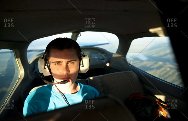 A teenage boy in the back seat of a small private plane as the sun sets.