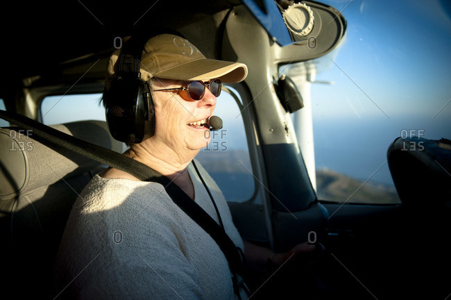 A woman pilots her small private plane as the sun sets.
