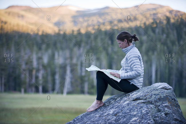 A woman, endurance athlete sits on a boulder in Big Meadow.