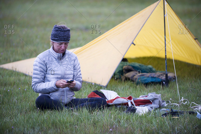 A woman, endurance athlete checking her smartphone at camp in Big Meadow.
