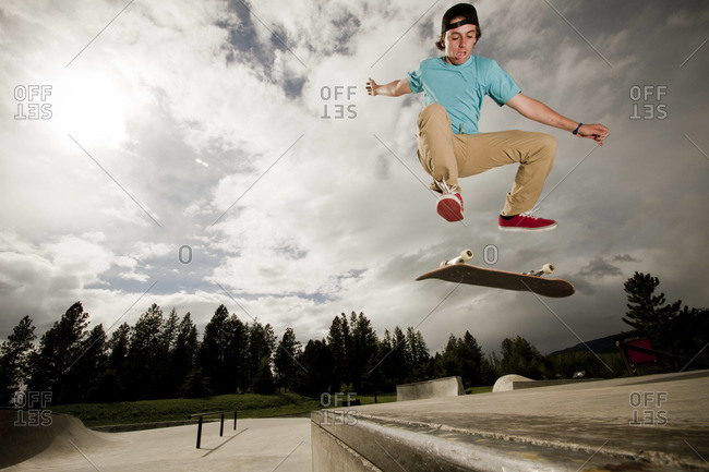 A skater kickflips his skateboard on a cloudy day at the skatepark in Whitefish, Montana.