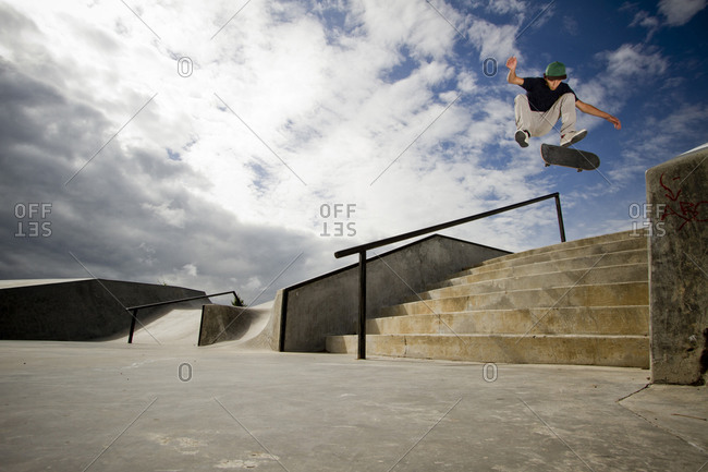 A young skateboarder, kickflips his skateboard over a 7-stair gap at the skatepark in Whitefish, Montana.