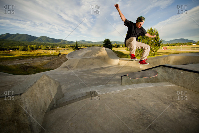 A skater flips his skateboard up a ramp at the skatepark in Whitefish, Montana on a cloudy summer day.