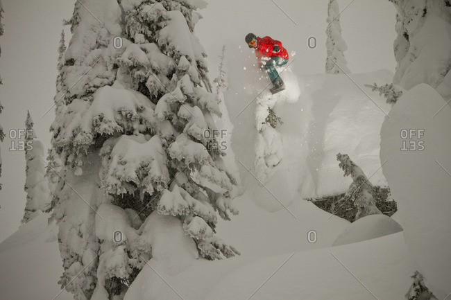 A snowboarder drops a small cliff on a cloudy winter day.