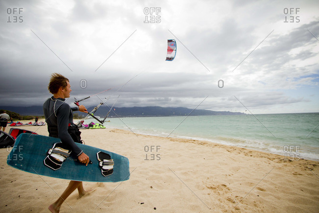 A kiteboarder prepares to hit the water on a beach on a cloudy summer day in Maui.
