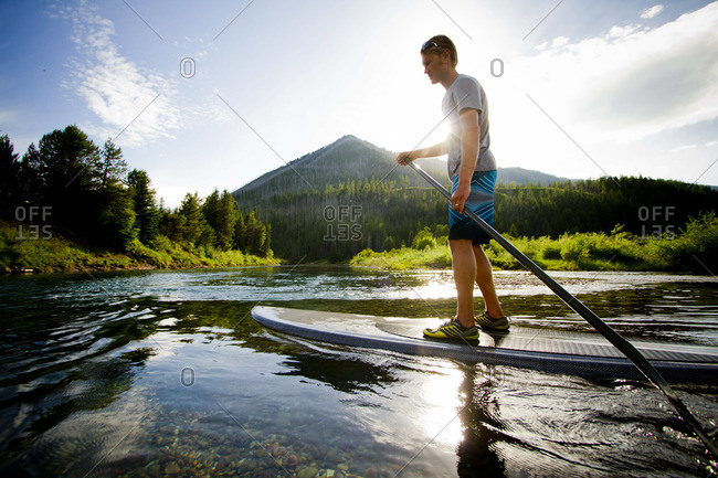 A young male paddles his paddleboard down McDonald Creek outside of Glacier National Park, Montana.