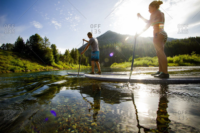 Two paddle boarders paddle down McDonald Creek outside of Glacier National Park, Montana on a sunny summer day.