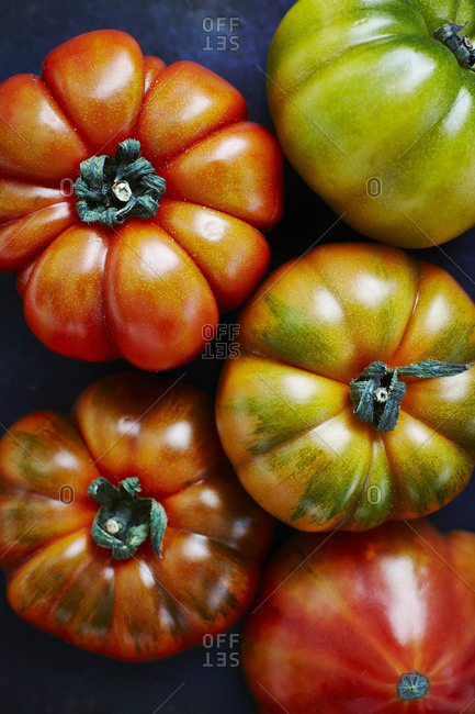 Five beef tomatoes on black ground, elevated view