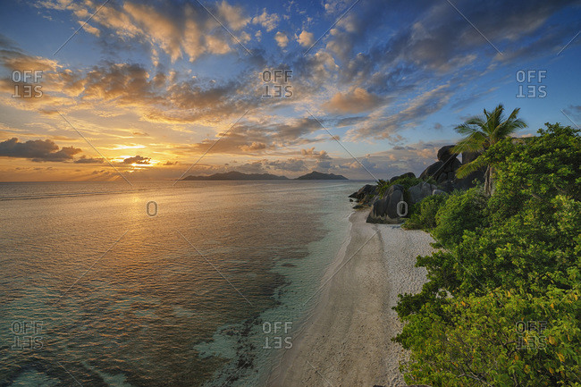 View to Anse Source d' Argent with sculpted rocks and palm trees at sunset, La Digue, Seychelles