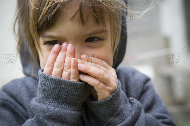 Little girl covering mouth with her hands