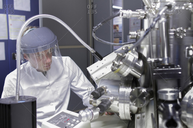 Scientist sitting in analytical laboratory with scanning electron microscope and spectrometer