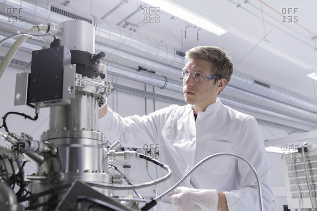 Scientist standing in analytical laboratory with scanning electron microscope and spectrometer