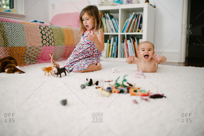 Older sister playing with plastic animals while a baby looks excited