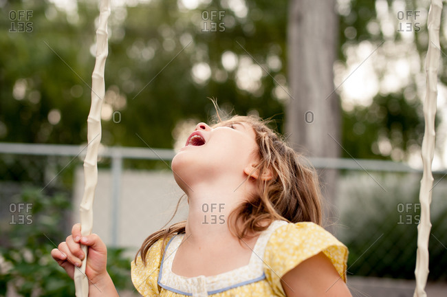 Girl swinging in the garden and looking up