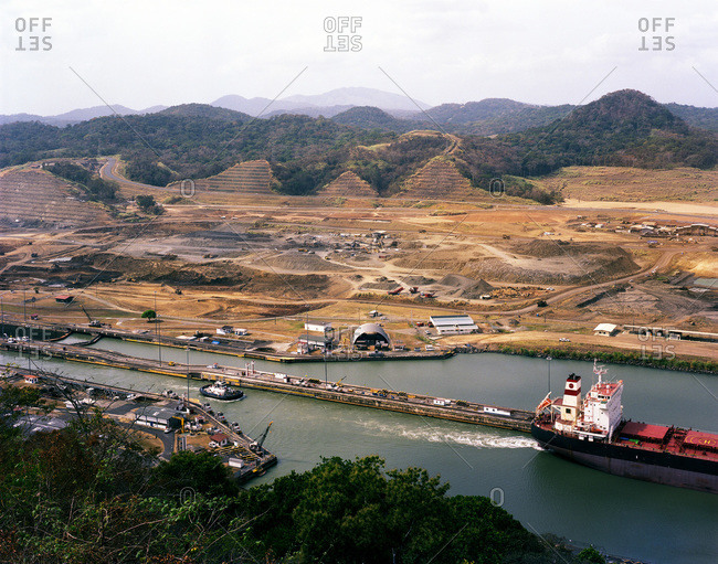 Cargo ship leaves the Pedro Miguel Locks at the Panama Canal with construction of the new Canal Expansion evident in the background