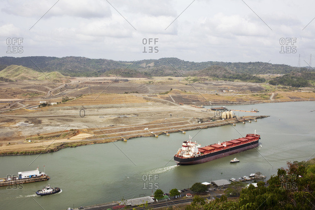 Cruise ship travelling thru the Pedro Miguel Locks at the Panama Canal with construction of the new Canal Expansion evident in the background