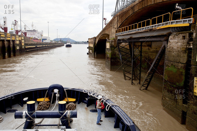 Crew member of a tugboat passing through the Miraflores Locks arranges his ropes while staring down a pelican