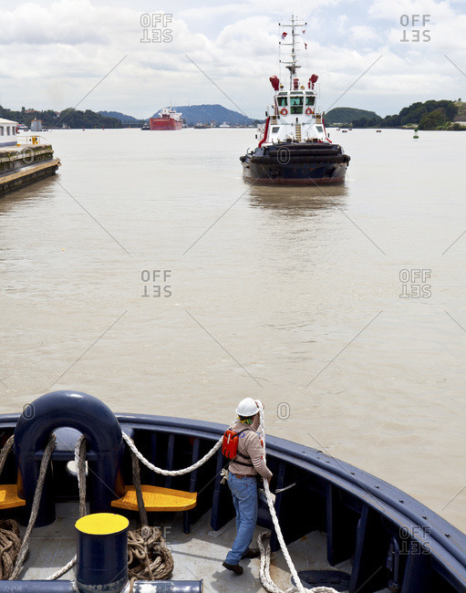 Crew member of a tugboat passing through the Miraflores Locks arranges his ropes, while another tugboat approaches in the background