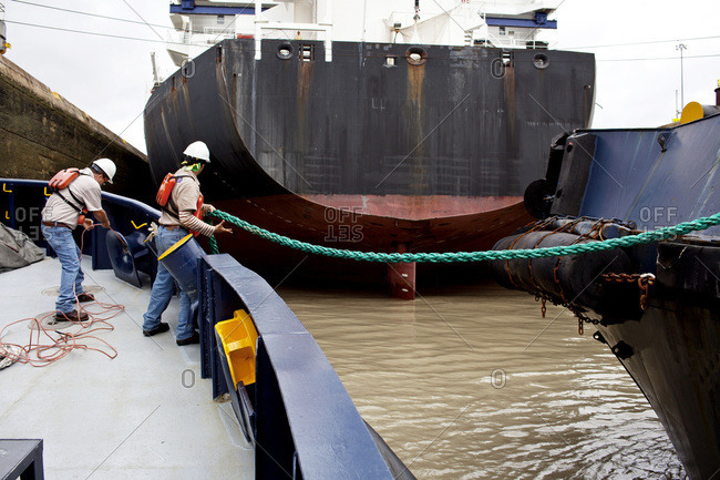 Crew members on a tugboat pull in rope to prepare for the transit through the Miraflores Locks on the Panama Canal