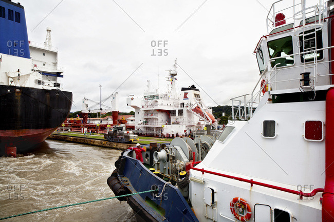 Crew member gives directions to the wheel house of a tugboat while transiting the Miraflores Locks of the Panama Canal