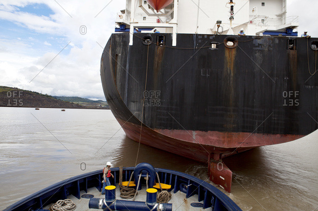 Crew member of a tugboat working with ropes while assisting a cargo ship and its transit of the Panama Canal