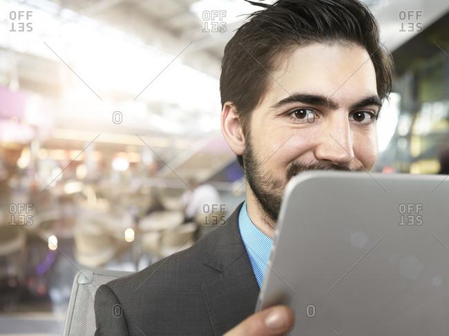 Portrait of smirking young businessman using digital tablet