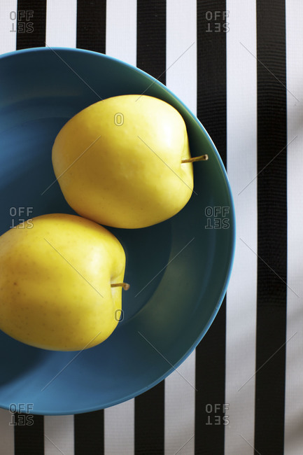 Top view of golden apples on striped table