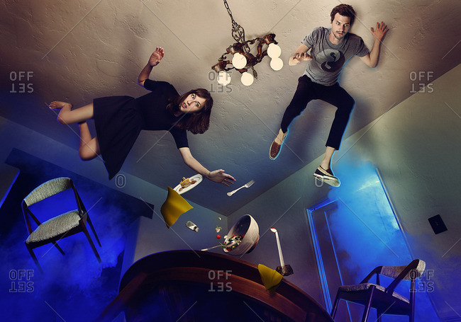 People floating in air above a dining table