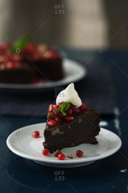 Slice of almond and chocolate cake with pomegranate