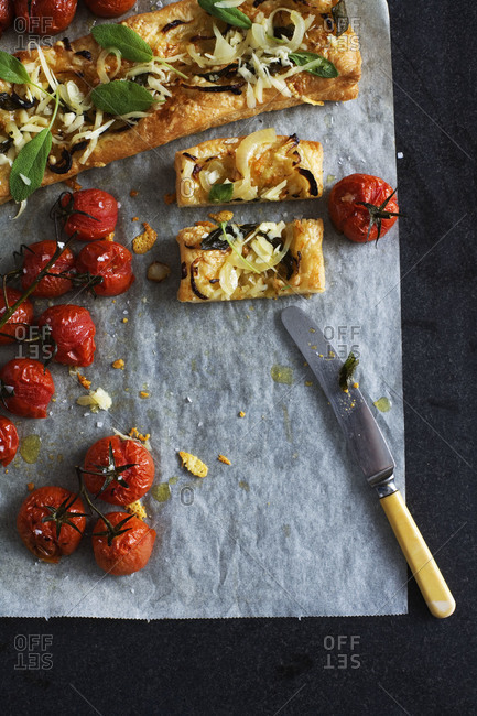 Puff pastry topped with red onion and cherry tomatoes