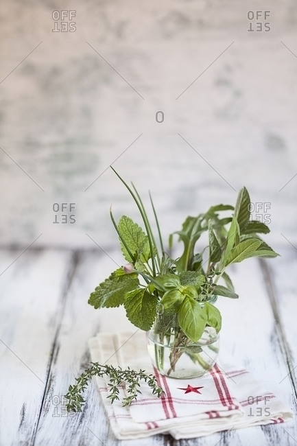 Different culinary herbs in a glass