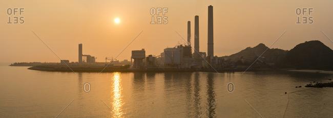 Panoramic view of Lamma Island, sunset over a coal-fired power plant in Yung Shue Wan bay, Hong Kong