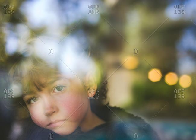 Portrait of boy looking out a window
