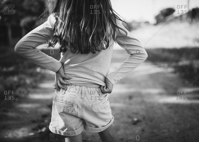 Back view of a girl standing on a dirt road
