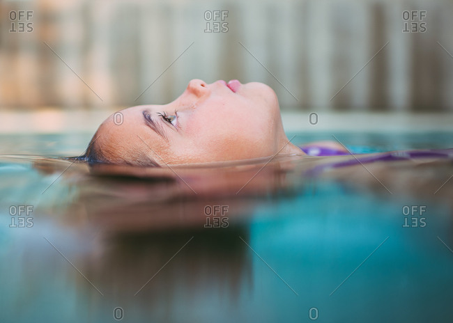 Side view of girl floating in a pool