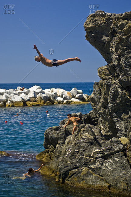 Manarola, Cinque Terre, Italy - August 19, 2010: Man diving of cliff into the ocean